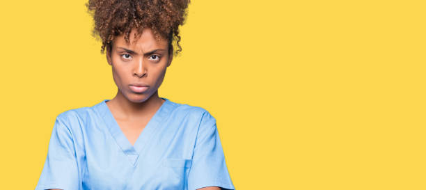 young african american doctor woman over isolated background skeptic and nervous, disapproving expression on face with crossed arms. negative person. - frowning stock photos and pictures