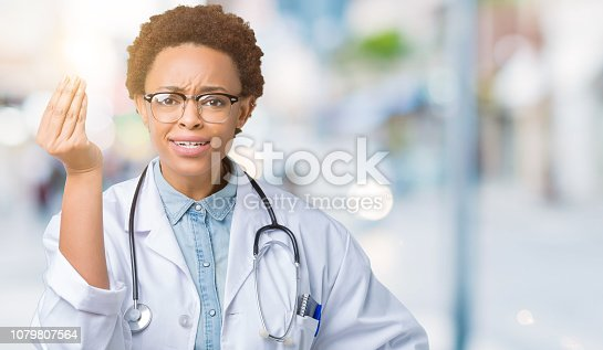 istock Young african american doctor woman wearing medical coat over isolated background Doing Italian gesture with hand and fingers confident expression 1079807564