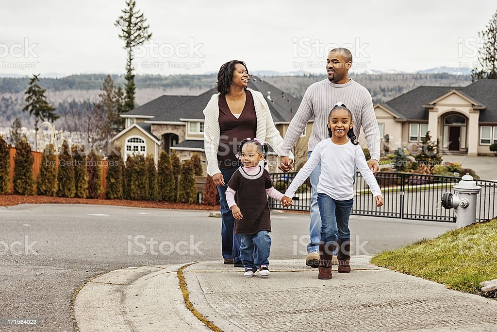 Young African American Family Taking a Stroll in the Neighborhood stock photo