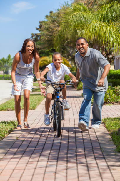 A young African American family with boy child riding his bicycle and his happy excited parents giving encouragement next to him stock photo