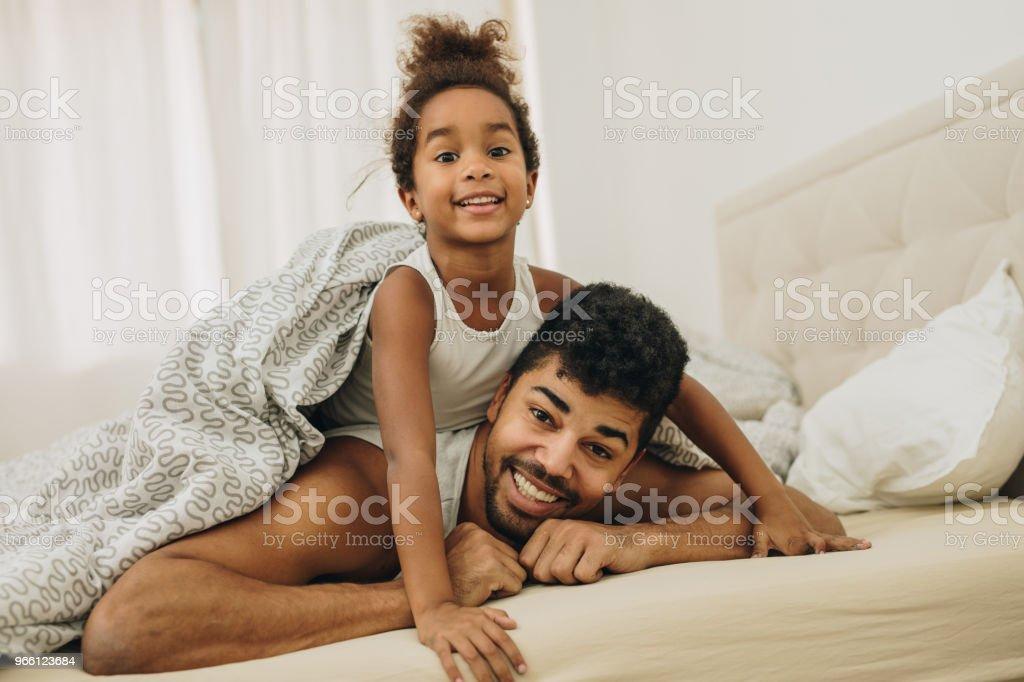 Ung African American far och dotter liggande på sängen på morgonen. - Royaltyfri Afrikanskt ursprung Bildbanksbilder