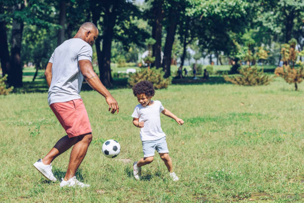 young african american father playing football with cute son in park stock photo