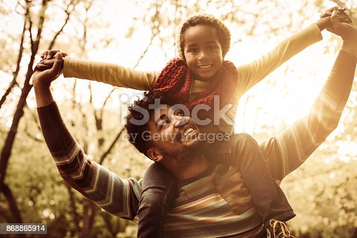 Smiling little girl sitting on father shoulders.