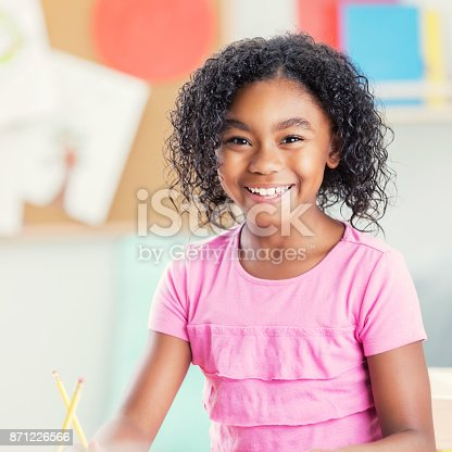 An adorable little girl sits at a desk at school and smiles for the camera.  She holds a pencil ready as she pauses to pose.  The photo is in square format.
