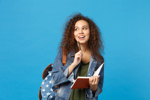 Young african american girl teen student in denim clothes, backpack hold books isolated on blue wall background studio portrait. Education in high school university college concept. Mock up copy space stock photo