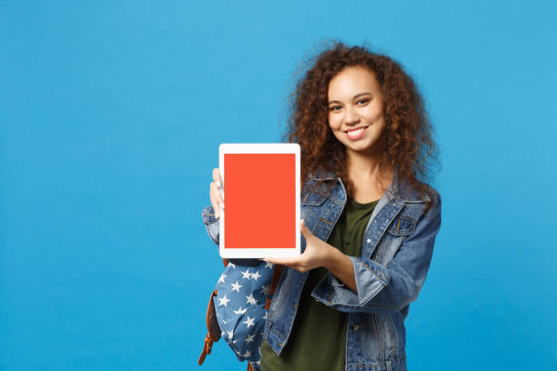 Young african american girl teen student in denim clothes, backpack hold pad pc isolated on blue background studio portrait. Education in high school university college concept. Mock up copy space. stock photo