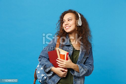 Young african american girl teen student in denim clothes, backpack headphones isolated on blue background studio portrait. Education in high school university college concept. Mock up copy space
