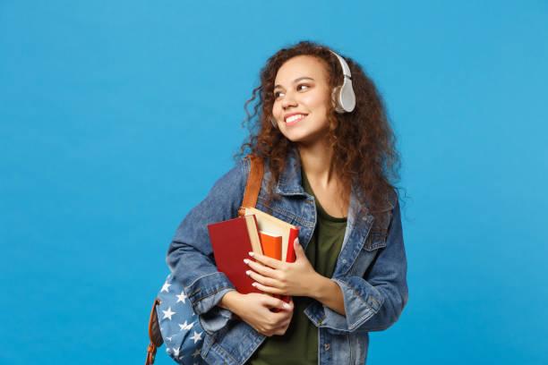 joven chica afroamericana estudiante adolescente en ropa de mezclilla, auriculares de mochila aislados en el retrato de fondo de pared azul de estudio. educación en el concepto universitario universitario de secundaria. mock up copia espacio - estudiante fotografías e imágenes de stock