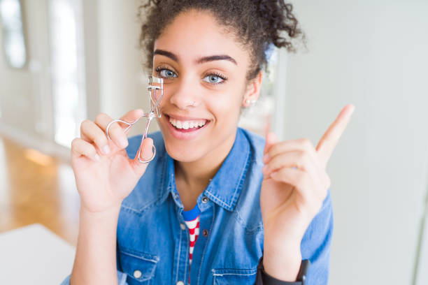 속눈썹 경기자를 사용 하 여 젊은 아프리카계 미국인 소녀 매우 행복 측면에 손과 손가락을 가리키는 - 속눈썹 컬러 뉴스 사진 이미지