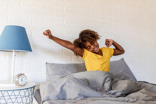 Young girl laying in bed and stretching
