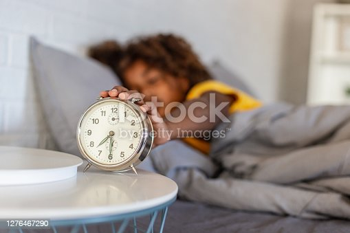 Young African American girl sleeping in bed and waking up