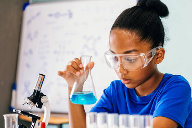 Young African American kid doing chemistry experiment stock photo