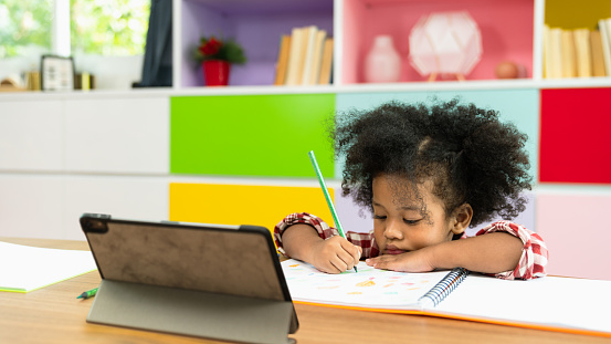 Young African American kid girl studying using digital tablet, preschool child study at home school. Children education, self isolation, coronavirus outbreak social distancing or homeschooling concept