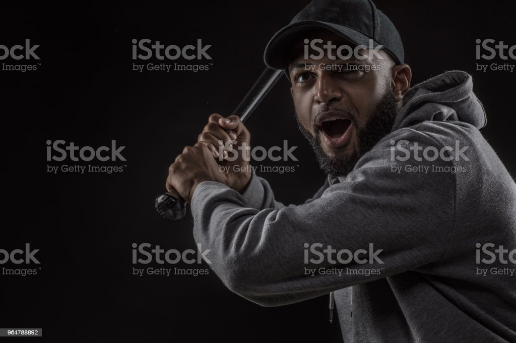 A young african american male baseball player swinging the bat in studio shot royalty-free stock photo