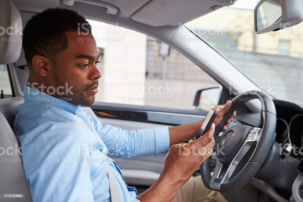 Young African American male driver using phone, in car view stock photo