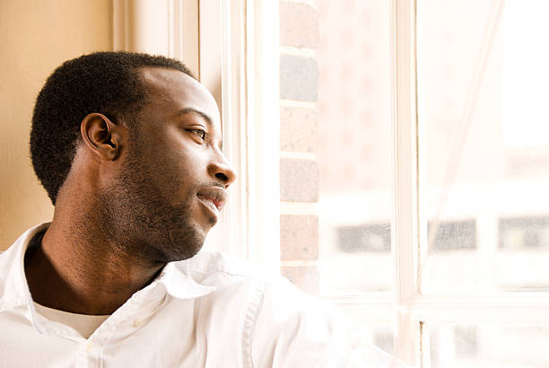 Young African American Male looking out window stock photo