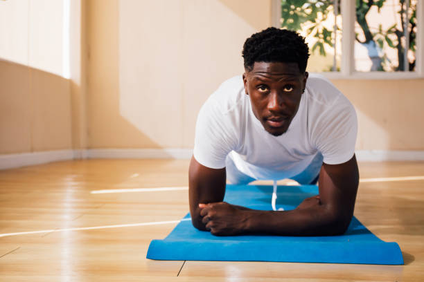 Young African American man doing a plank exercise at gym stock photo