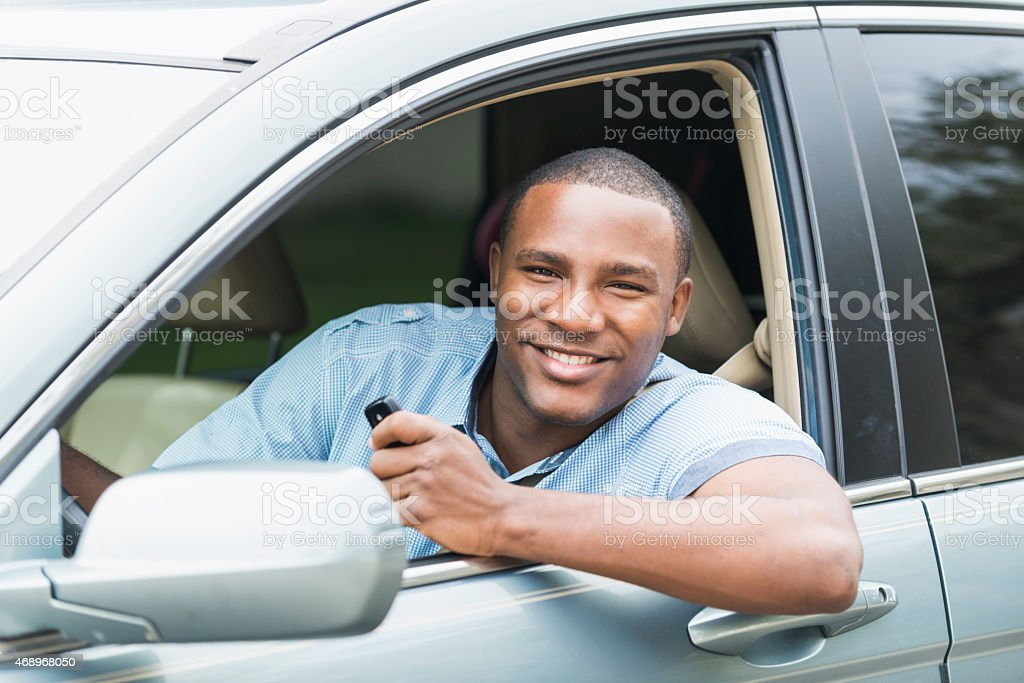 Young African American man driving car stock photo