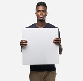 istock Young african american man holding a banner with a confident expression on smart face thinking serious 1043958626
