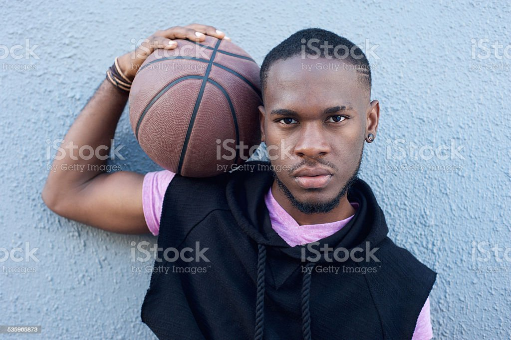 Young african american man holding basketball stock photo