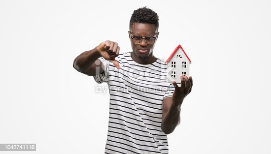 Young african american man holding house with angry face, negative sign showing dislike with thumbs down, rejection concept