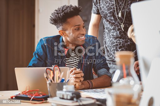 918746260istockphoto Young african american man in meeting with coworkers 667042588