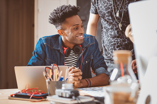 918746260 istock photo Young african american man in meeting with coworkers 667042588