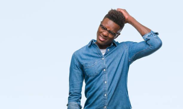 afrikanische amerikanische jüngling über isolierte hintergrund verwirren und wundern sich über frage. unsicher mit zweifel, mit der hand auf kopf denken. nachdenklich-konzept. - verwirrung stock-fotos und bilder