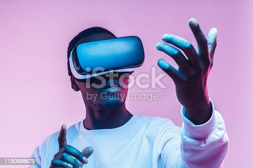 1090878574istockphoto Young african american man playing game using VR glasses, enjoying 360 degree virtual reality headset for gaming, isolated on pink background 1150698673