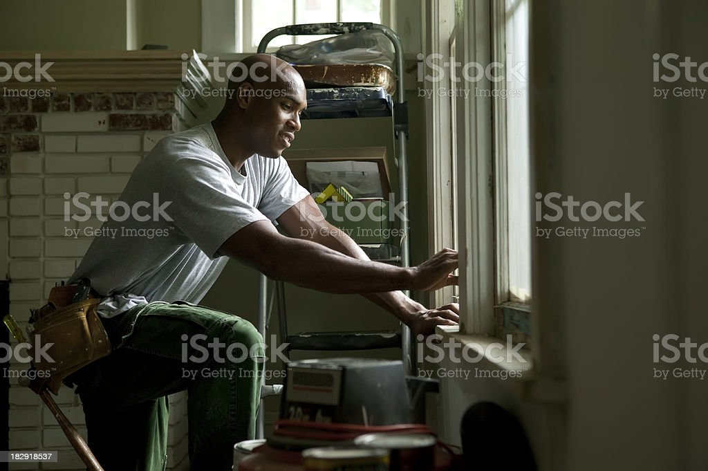 Young African American man remodeling his home. stock photo