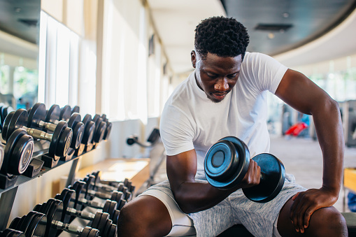 Young African American man sitting and lifting a dumbbell with the rack at gym