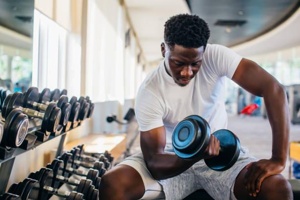 joven afroamericano sentado y levantando una mancuerna con el estante en el gimnasio - culturismo fotografías e imágenes de stock