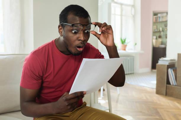 jovem americano africano, sentada no sofá moderno apartamento com a boca aberta, segurando a conta de serviço público com altas taxas, gerado óculos num gesto wow ou surpresa - alto descrição geral - fotografias e filmes do acervo