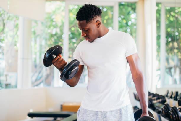 Junger afroamerikanischer Mann steht und hebt eine Hantel mit dem Rack im Fitnessstudio – Foto