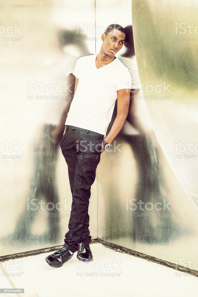 Young African American Man standing by metal silver wall in New York, thinking photo libre de droits