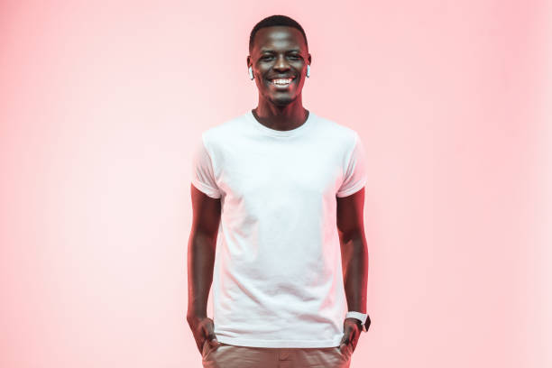 Young african american man standing with hands in pockets, wearing blank white t-shirt with copy space for your logo or text, isolated on pink background Young african american man standing with hands in pockets, wearing blank white t-shirt with copy space for your logo or text, isolated on pink background white t shirt stock pictures, royalty-free photos & images