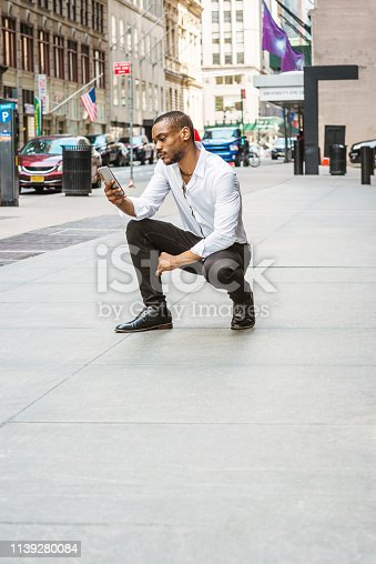 istock Young African American Man texting on street in New York 1139280084