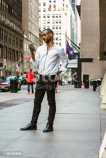 istock Young African American Man texting on street in New York 1139280635