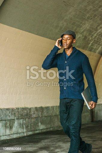Young African American Man wearing  blue shawl collar cardigan sweater, black pants, flat cap, holding laptop computer, talking on cell phone, walking through under street bridge in New York City.