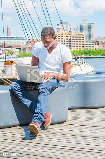 istock Young African American Man traveling, working on laptop computer in New York 675448974