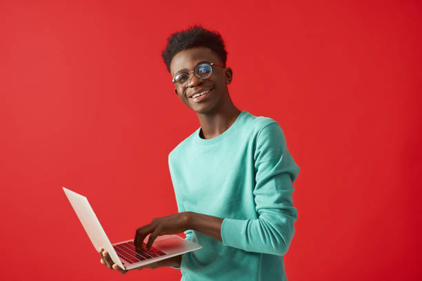 Young African American man using laptop and smiling stock photo