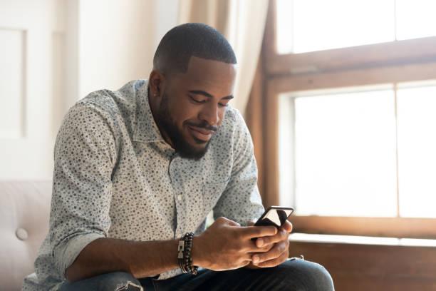 jonge afro-amerikaanse man met behulp van smartphone app zitten op de bank - daten stockfoto's en -beelden