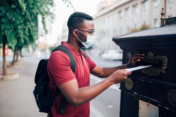 Young African American man voting by mail stock photo