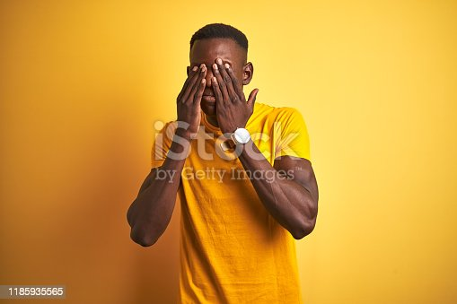 626964348istockphoto Young african american man wearing casual t-shirt standing over isolated yellow background rubbing eyes for fatigue and headache, sleepy and tired expression. Vision problem 1185935565