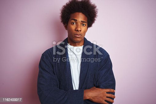 istock Young african american man wearing pajama standing over isolated pink background skeptic and nervous, disapproving expression on face with crossed arms. Negative person. 1162400017