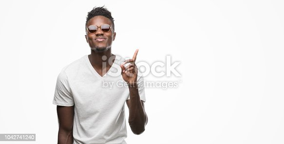 Young african american man wearing sunglasses surprised with an idea or question pointing finger with happy face, number one
