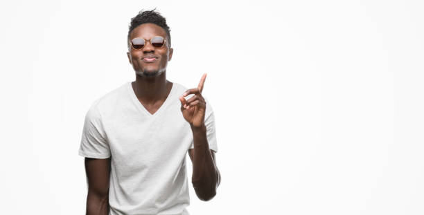 Young african american man wearing sunglasses surprised with an idea or question pointing finger with happy face, number one Young african american man wearing sunglasses surprised with an idea or question pointing finger with happy face, number one cool attitude stock pictures, royalty-free photos & images