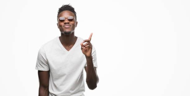 genç afro-amerikan giyen güneş gözlüğü bir fikirle şaşırmış adam ya da gülen yüz, bir numara ile işaret parmağı soru - havalı tutum stok fotoğraflar ve resimler