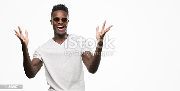 istock Young african american man wearing sunglasses very happy and excited, winner expression celebrating victory screaming with big smile and raised hands 1043958714