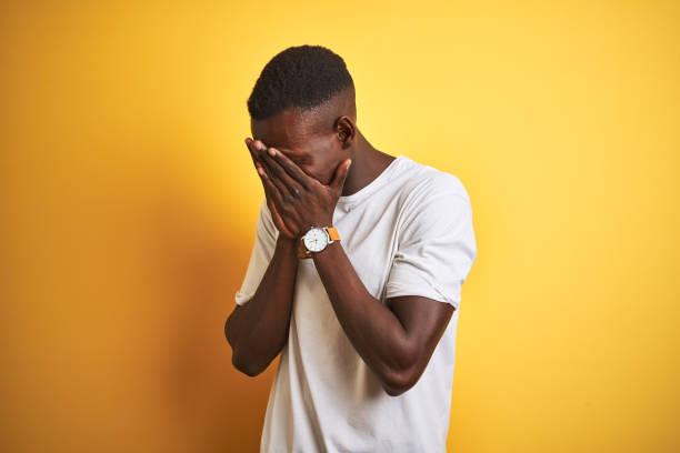 joven afroamericano con camiseta blanca de pie sobre fondo amarillo aislado con expresión triste cubriendo la cara con las manos mientras llora. concepto de depresión. - vergüenza fotografías e imágenes de stock